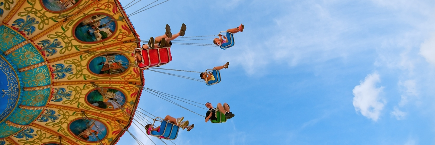 Header image: children on a fairground swing ride with blue sky above